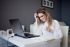 Σπουδαστής ή freelancer, εργαζόμενος στο σπίτι με το lap-top Η γοητεία της νέας γυναίκας κάθεται μπροστά από το όργανο ελέγχου με στοκ εικόνες