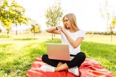 Σπουδαστής κοριτσιών με τα γυαλιά, που κάθονται στο πάρκο με ένα lap-top και στοκ εικόνες