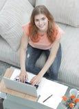 Σπουδαστής κοριτσιών που εργάζεται στο lap-top καθμένος κοντά σε ένα τραπεζάκι σαλονιού Στοκ εικόνα με δικαίωμα ελεύθερης χρήσης