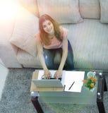 Σπουδαστής κοριτσιών που εργάζεται στο lap-top καθμένος κοντά σε ένα τραπεζάκι σαλονιού Στοκ Φωτογραφία