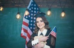 Σπουδαστής με τα βιβλία στο πάρκο ενάντια στην ΑΜΕΡΙΚΑΝΙΚΗ σημαία Κομψό άτομο στο υπόβαθρο με τη σημαία των ΗΠΑ English πλίθας Στοκ Εικόνες