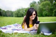 Σπουδαστής νέων κοριτσιών που μιλά στο τηλέφωνο, που βρίσκεται στη χλόη στο πάρκο Στοκ Φωτογραφία