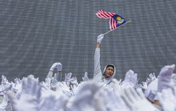 Σπουδαστής που κυματίζει τη σημαία της Μαλαισίας γνωστή επίσης ως Jalur Gemilang Στοκ Φωτογραφίες