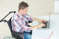 Σπουδαστής στην αναπηρική καρέκλα δακτυλογράφηση στο lap-top Στοκ φωτογραφία με δικαίωμα ελεύθερης χρήσης