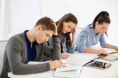 Σπουδαστές με τα σημειωματάρια και PC ταμπλετών στο σχολείο Στοκ εικόνα με δικαίωμα ελεύθερης χρήσης