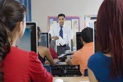 Σπουδαστές με τον καθηγητή στη σύγχρονη τάξη στοκ εικόνες