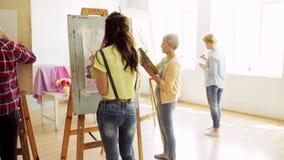 Σπουδαστές με easels που χρωματίζουν στο σχολείο τέχνης απόθεμα βίντεο
