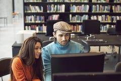 Σπουδαστές που βρίσκουν τις πληροφορίες για τη μελέτη για τον υπολογιστή στη βιβλιοθήκη Στοκ εικόνα με δικαίωμα ελεύθερης χρήσης