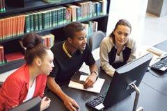 Σπουδαστές που βρίσκουν τις πληροφορίες για τον υπολογιστή για το σχολικό πρόγραμμα Στοκ εικόνα με δικαίωμα ελεύθερης χρήσης