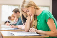 Σπουδαστές που γράφουν τις σημειώσεις στην τάξη Στοκ Εικόνες