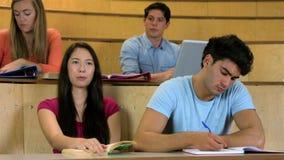 Σπουδαστές που κάθονται ο ένας εκτός από τον άλλον μαθαίνοντας απόθεμα βίντεο