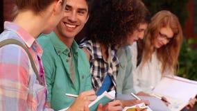 Σπουδαστές που κάθονται σε μια σειρά που γράφει στα σημειωματάρια απόθεμα βίντεο