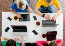 Σπουδαστές που κάθονται στον πίνακα που χρησιμοποιεί τους υπολογιστές στοκ φωτογραφίες με δικαίωμα ελεύθερης χρήσης