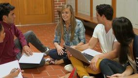 Σπουδαστές που κάθονται στο πάτωμα και την ομιλία απόθεμα βίντεο