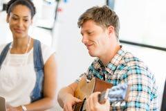 Σπουδαστές που κάθονται στο πάτωμα με μια κιθάρα playng Στοκ φωτογραφία με δικαίωμα ελεύθερης χρήσης