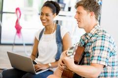 Σπουδαστές που κάθονται στο πάτωμα με μια κιθάρα playng Στοκ Φωτογραφία