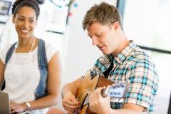 Σπουδαστές που κάθονται στο πάτωμα με μια κιθάρα playng Στοκ Εικόνες