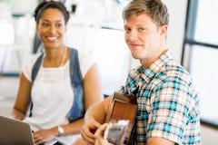 Σπουδαστές που κάθονται στο πάτωμα με μια κιθάρα playng Στοκ Εικόνα