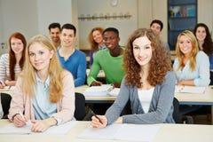 Σπουδαστές που κάθονται στο πανεπιστήμιο Στοκ φωτογραφία με δικαίωμα ελεύθερης χρήσης