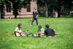 Σπουδαστές που παίζουν την κιθάρα και που έχουν τη διασκέδαση στο πάρκο Στοκ φωτογραφίες με δικαίωμα ελεύθερης χρήσης