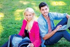 Σπουδαστές φίλων Κορίτσι-σπουδαστής και άνδρας σπουδαστής που κρατούν ένα lap-top Στοκ Φωτογραφία