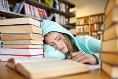 Σπουδαστής ή γυναίκα με τα βιβλία που κοιμούνται στη βιβλιοθήκη Στοκ εικόνα με δικαίωμα ελεύθερης χρήσης