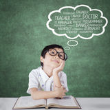 Σπουδαστής δημοτικού σχολείου που σκέφτεται τις μελλοντικές εργασίες στοκ φωτογραφία