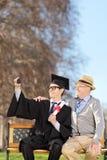 Σπουδαστής και ο υπερήφανος πατέρας του που παίρνουν selfie στο πάρκο στοκ φωτογραφία με δικαίωμα ελεύθερης χρήσης