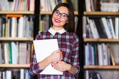 Σπουδαστής κοριτσιών με τα γυαλιά που διαβάζει τα βιβλία στη βιβλιοθήκη Στοκ Φωτογραφίες