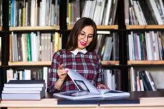 Σπουδαστής κοριτσιών με τα γυαλιά που διαβάζει τα βιβλία στη βιβλιοθήκη Στοκ εικόνα με δικαίωμα ελεύθερης χρήσης