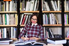 Σπουδαστής κοριτσιών με τα γυαλιά που διαβάζει τα βιβλία στη βιβλιοθήκη Στοκ Εικόνες