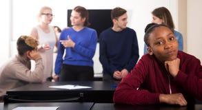 Σπουδαστής κοριτσιών που είναι ντροπαλός μεταξύ των συμμαθητών Στοκ φωτογραφία με δικαίωμα ελεύθερης χρήσης