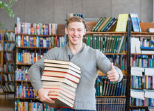 Σπουδαστής με τα βιβλία σωρών που παρουσιάζουν αντίχειρες στη βιβλιοθήκη κολλεγίων Στοκ φωτογραφίες με δικαίωμα ελεύθερης χρήσης