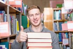 Σπουδαστής με τα βιβλία σωρών που παρουσιάζουν αντίχειρες στη βιβλιοθήκη κολλεγίων Στοκ Εικόνα
