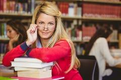Σπουδαστής με τα γυαλιά ανάγνωσης που κλίνουν σε έναν σωρό των βιβλίων στοκ φωτογραφίες