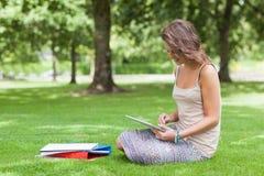 Σπουδαστής με το PC ταμπλετών και βιβλία στο πάρκο Στοκ Εικόνες