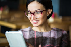 Σπουδαστής - νέα συνεδρίαση γυναικών ή κοριτσιών με τον υπολογιστή ταμπλετών σε έναν καφέ που διαβάζει ένα eBook Στοκ Φωτογραφία