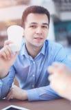 Σπουδαστής νεαρών άνδρων που χρησιμοποιεί τον υπολογιστή ταμπλετών στον καφέ Στοκ εικόνα με δικαίωμα ελεύθερης χρήσης