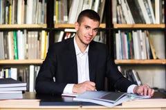 Σπουδαστής που διαβάζει ένα βιβλίο στη βιβλιοθήκη Τύπος που διαβάζει ένα βιβλίο σε μια βιβλιοθήκη Στοκ Εικόνες
