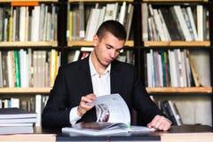 Σπουδαστής που διαβάζει ένα βιβλίο στη βιβλιοθήκη Τύπος που διαβάζει ένα βιβλίο σε μια βιβλιοθήκη Στοκ Φωτογραφία