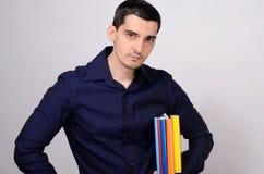 Σπουδαστής που κρατά έναν σωρό των βιβλίων κάτω από το βραχίονά του. Δάσκαλος με τα ζωηρόχρωμα βιβλία στο χέρι του. Στοκ εικόνα με δικαίωμα ελεύθερης χρήσης