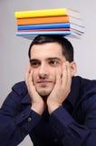 Σπουδαστής που κρατά έναν σωρό των βιβλίων στο κεφάλι του. Στοκ φωτογραφία με δικαίωμα ελεύθερης χρήσης