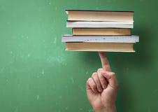 Σπουδαστής που κρατά ψηλά τα βιβλία με ένα δάχτυλο Στοκ εικόνα με δικαίωμα ελεύθερης χρήσης