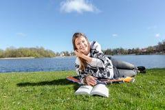 Σπουδαστής που μαθαίνει με ένα βιβλίο και που γελά στη κάμερα Στοκ φωτογραφία με δικαίωμα ελεύθερης χρήσης