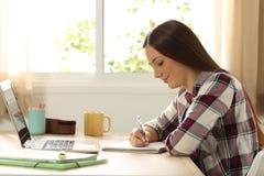 Σπουδαστής που μελετά και που παίρνει τις σημειώσεις στο σπίτι Στοκ Εικόνα