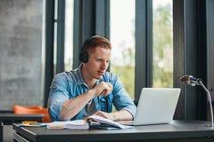 Σπουδαστής που μελετά με τα βιβλία και το lap-top στη βιβλιοθήκη στοκ φωτογραφία με δικαίωμα ελεύθερης χρήσης