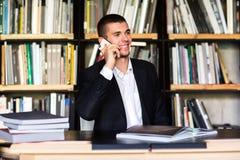 Σπουδαστής που μιλά στο τηλέφωνο στη βιβλιοθήκη Στοκ Εικόνες