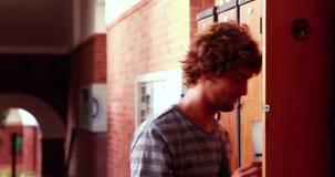 Σπουδαστής που περπατά και που ανοίγει το ντουλάπι του απόθεμα βίντεο
