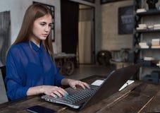 Σπουδαστής που προετοιμάζεται για τις κατηγορίες που κάνουν σερφ το Διαδίκτυο στη συνεδρίαση lap-top της στον πίνακα στον καθιερώ στοκ εικόνες με δικαίωμα ελεύθερης χρήσης
