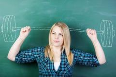 Σπουδαστής που σφίγγει τις πυγμές με Barbell που επισύρονται την προσοχή στον πίνακα κιμωλίας Στοκ Φωτογραφία